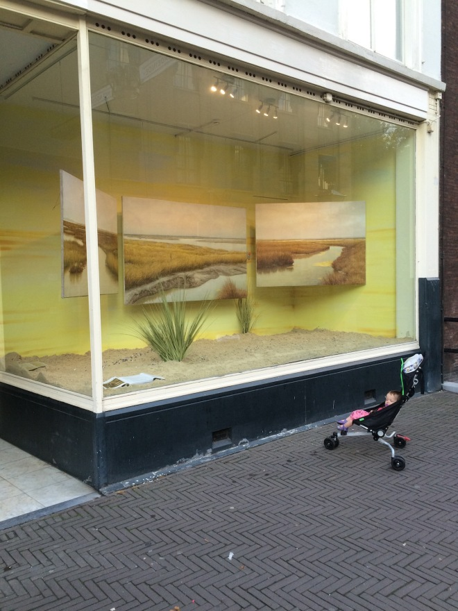 Finally heading home, artist and subject find a beach in a shop window. The art becomes part of the art, the circle of creation (and of the centre of Den Haag, roughly 3 kilometres) is complete